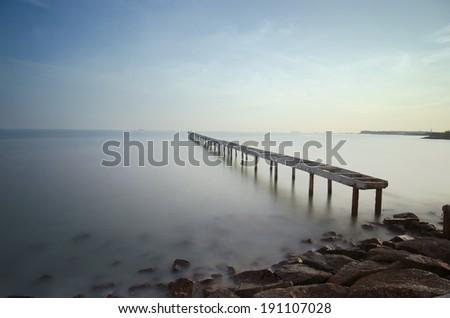 Broken bridge and waves crashing on sea at during sunset - stock photo