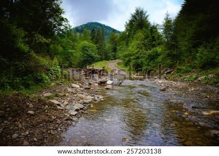 Broken bridge on the mountain river in the Carpathians - stock photo