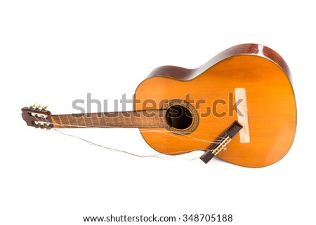 Broken brown classical guitar with detached bridge from body isolated in white background - stock photo