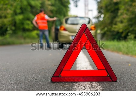 Broken car on the road and driver with red warning sign