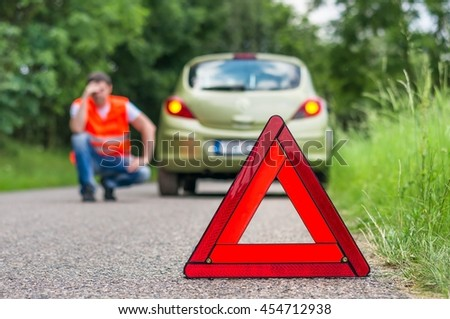 Broken car on the road and unhappy driver with red warning triangle