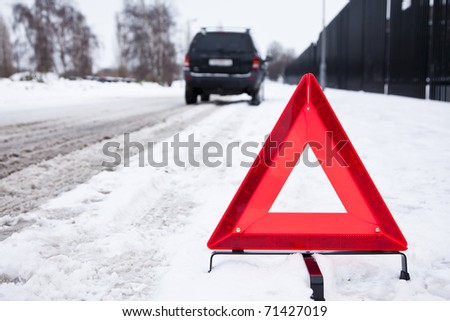 Broken car parked with a warning triangle in a snowy street - stock photo