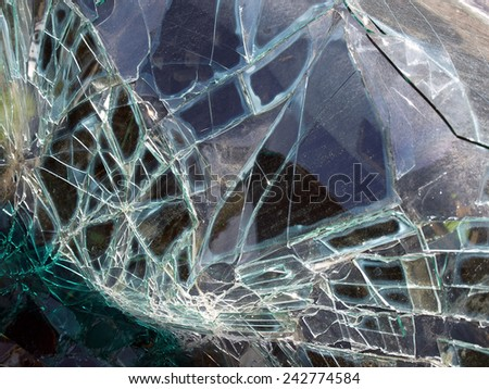 Broken car windscreen with glass pieces and crashes close up        - stock photo