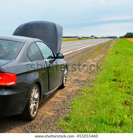 Broken car with open hood stopped on a verge of country road. Beautiful landscape. Road lines converge on the horizon. Panoramic view. Stop halfway out of town. Picturesque rural area. Summer trip. - stock photo