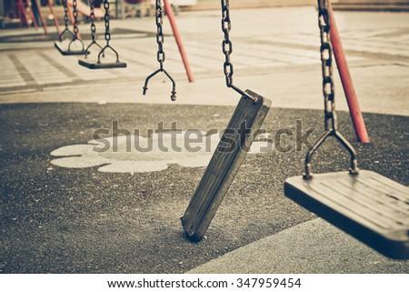 Broken chain swing in playground - stock photo