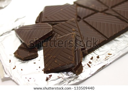 Broken chocolate bar on a foil - stock photo
