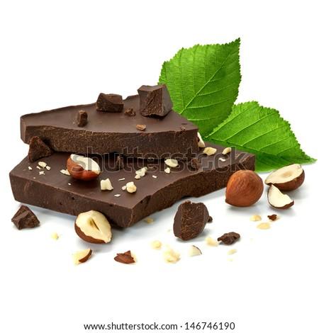Broken chocolate blocks with hazelnuts on white background - stock photo