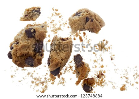 Broken chocolate chip cookies scattered over white background - stock photo
