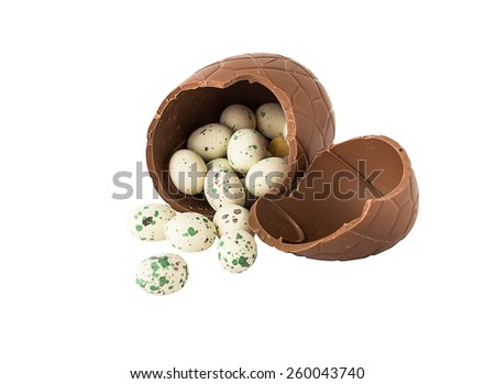 Broken chocolate egg with small candy eggs isolated on white - stock photo