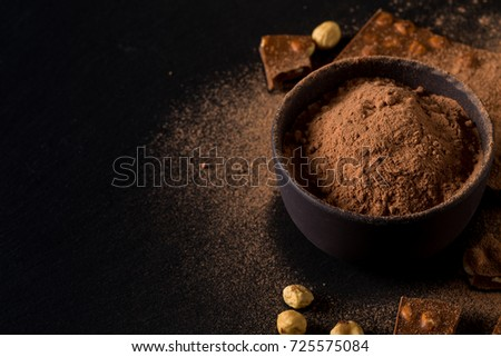 Broken chocolate nuts pieces and cocoa powder on dark background