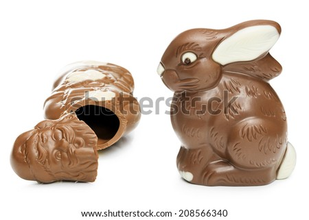 Broken chocolate Santa Claus and Easter bunny over white background