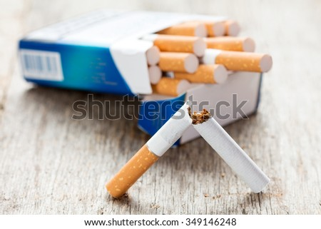 Broken cigarette in a front of full package - stock photo