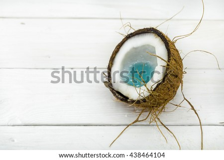 broken coconut, white wooden background, tasty and healthy - stock photo