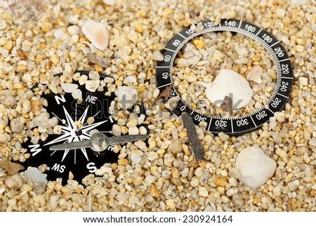 broken compass on sand  - stock photo