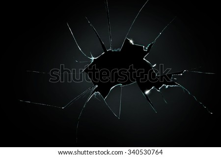 broken cracked glass with big hole over black background - stock photo