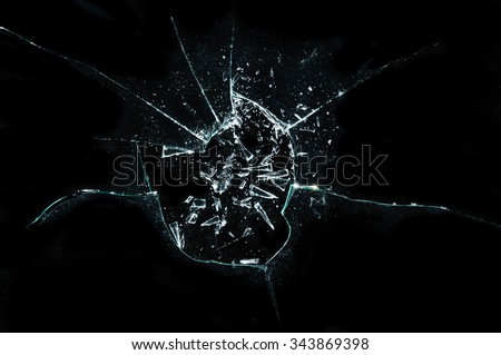 broken cracked glass with hole over black background  - stock photo