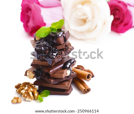 Broken dark chocolate bar and roses isolated on white background - stock photo