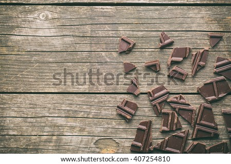 broken dark chocolate on old wooden background - stock photo