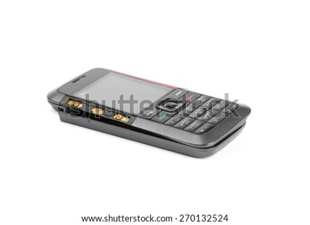 Broken disassembled cell phone cyrillic keypad over a white background put on its rear cover lid. - stock photo