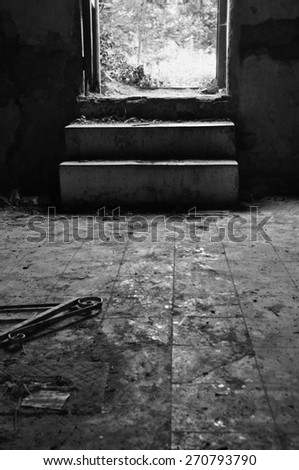 Broken door frame and debris on dirty tiled floor of an abandoned house. Black and white. - stock photo