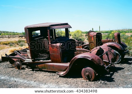 Broken down and rusty old trucks with no tires in the desert