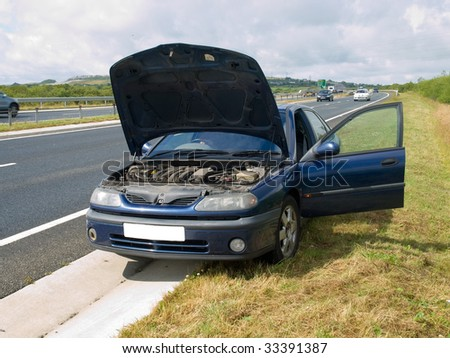 Broken down car on the side of a busy road - stock photo
