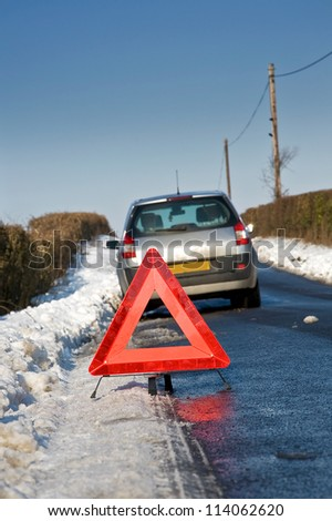 Broken down motor vehicle with red warning triangle in winter snow conditions