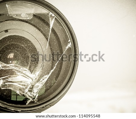 Broken DSLR camera lens with grunge effect - stock photo