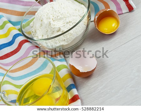 broken egg in bowl and flour on a white table with colored towel
