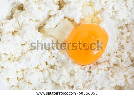 broken egg on white cottage cheese