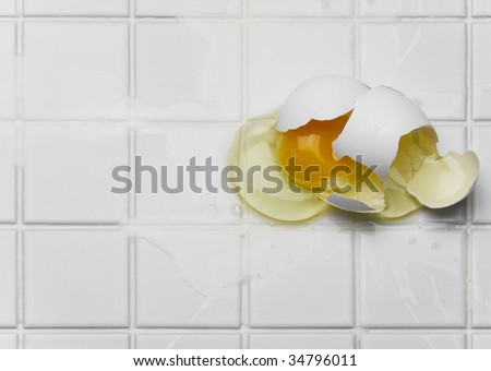 Broken egg on white tiles