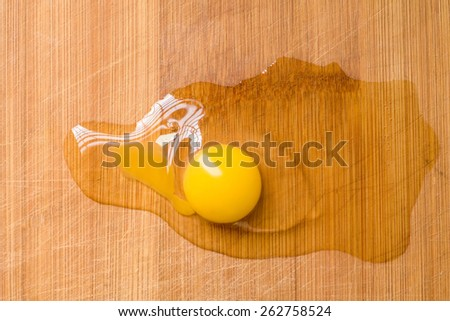 Broken egg on woody plank  from above view - stock photo