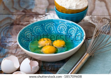 Broken eggs in a bowl, flour and various tools next to them on wooden table.  - stock photo