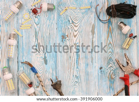 broken energy saving lamps, pliers and wire on a blue background - stock photo