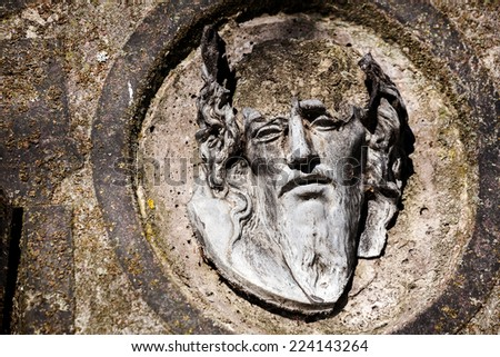 Broken face of Jesus Christ on old tombstone  - stock photo