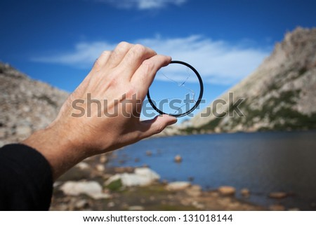 Broken filter to the camera lens on the background of the mountain landscape - stock photo