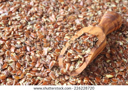 Broken flax seeds in wooden scoops