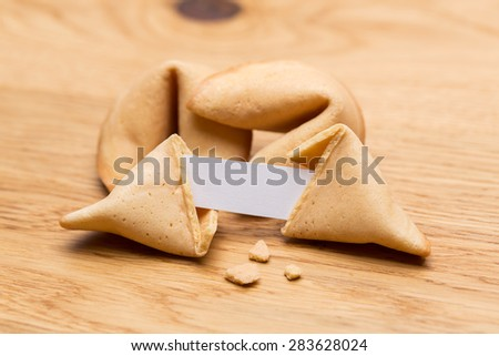 broken fortune cookie with a note on wooden table - stock photo