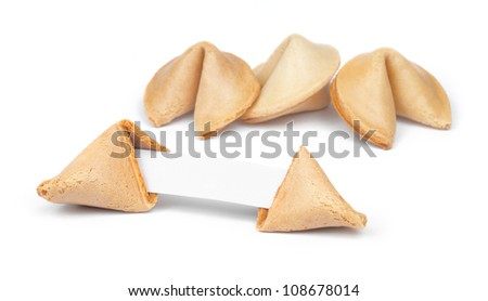 Broken fortune cookie with fortune paper in front of a few other cookies isolated on white. - stock photo