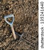 Broken garden fork - metaphor, tired gardener, rocky soil background - stock photo