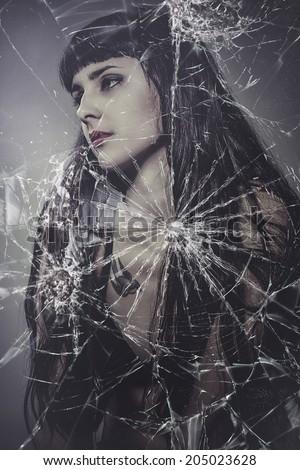 broken glass, beautiful brunette woman with very long hair - stock photo