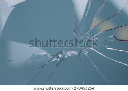 broken glass blue background - stock photo