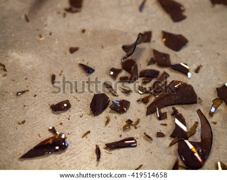 Broken Glass Bottle Pieces on a Cement Floor - stock photo