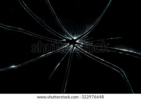 broken glass - cracked with hole over black - stock photo
