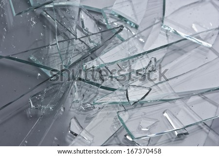 Broken glass fragments above grey. Abstract background texture - stock photo