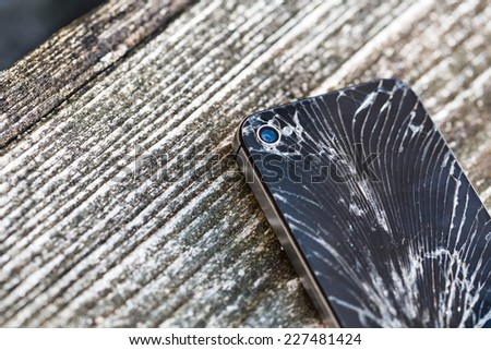 Broken glass of smart phone on the grunge wood. Copy space. Selective focus. Low depth of field. - stock photo