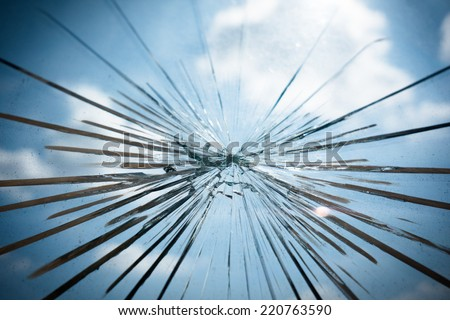 Broken Glass with Blue Sky and Clouds in Background. - stock photo