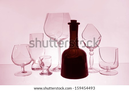 Broken glasses and bottle of wine in pink