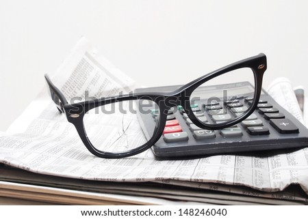 Broken glasses  and old calculator on stock report -  losses in stock trading concept