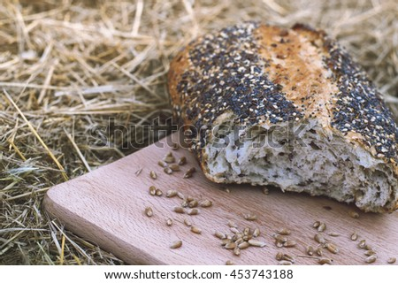 Broken grain bread and wheat outdoors